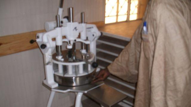 Un détenu manie une partageuse, l'outil servant à couper la farine lors de la fabrication du pain.