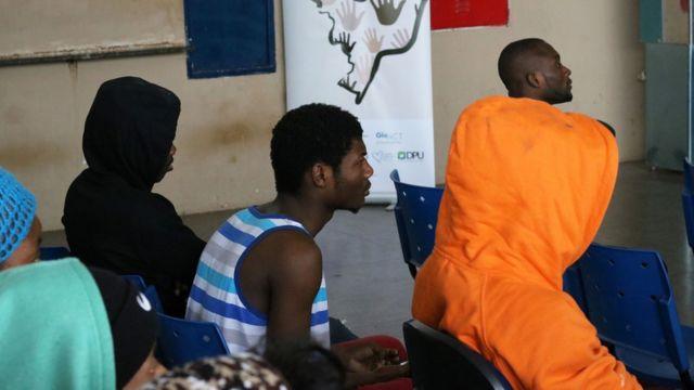 Haitianos sentados esperam por atendimento em dependências de órgão público