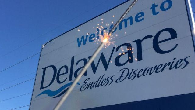 Una luz de bengala encendida frente a un letrero de bienvenida a Delaware.