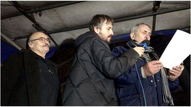 Branislav Trifunović (u sredini) drži mikrofon za novinara Milanu Jovanović (desno) u tokom obraćanja učesnicima protesta. Karikaturista Dušan Petričić (levo) takođe je bio među govornicima.