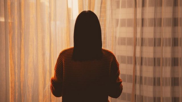 Sombra de mulher, de costas para câmera, olhando para fora da janela