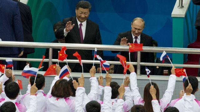 中国の習近平氏(左)はロシアのウラジーミル・プーチン大統領を中国に招き、アイスホッケーの親善試合に招待した
