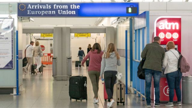 """People at an airport walking under a sign saying """"arrivals from the European Union""""."""