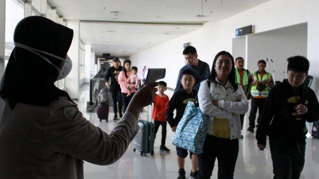 Petugas melakukan pendeteksi suhu tubuh (thermal scanner) saat penumpang pesawat tiba di terminal 2 Bandara Juanda Surabaya, Jawa Timur, Rabu (22/1/2020).
