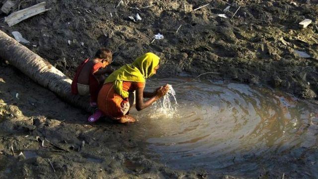 Dos niños recogen agua en un pozo