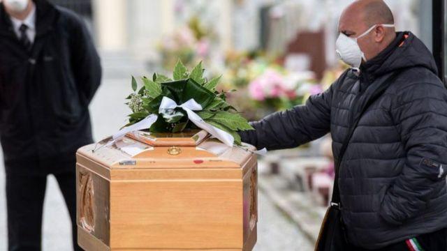Homem de máscara põe a mão sobre caixão durante um velório na Itália