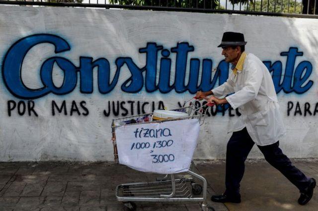 Un hombre pasa con su carro de supermercado frente a una pintada que hace referencia a las elecciones para una Asamblea Constituyente en Venezuela.