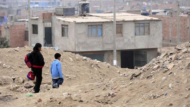 Niño caminando al colegio en una zona pobre de Lima.