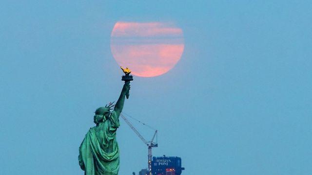 """La """"súper Luna de gusano"""" detrás de la Estatua de la Libertad en Nueva York, el 20 de marzo de 2019."""