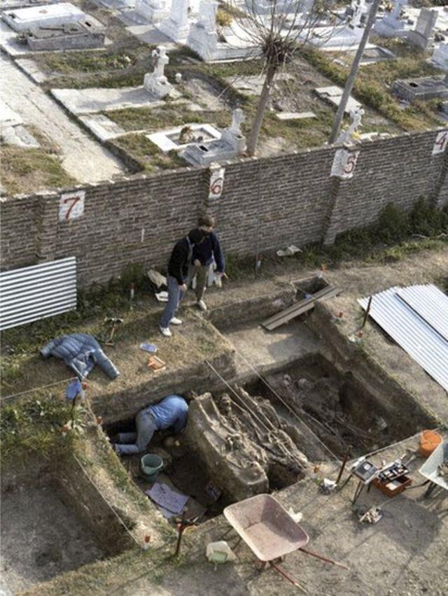 Hombres y mujes excavando en un cementerio.