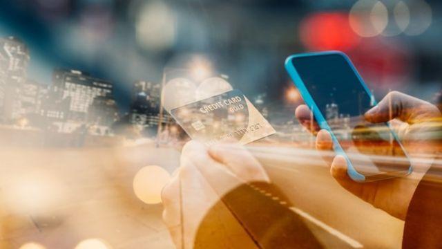 Una persona sosteniendo su tarjeta de crédito en una mano y su teléfono en la otra