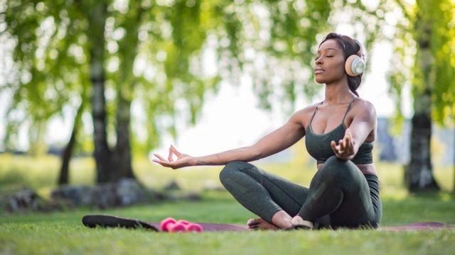 Una mujer meditando en un área verde.
