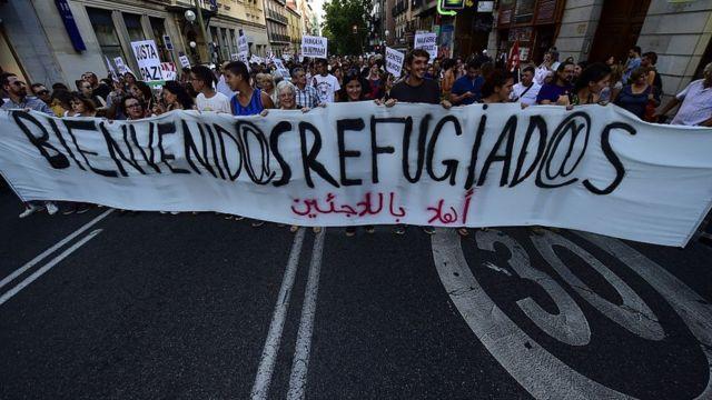 """Una pancarta de """"Bienvenidos Refugiados"""" en una manifestación."""