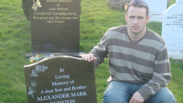 Daniel Durston ao lado do túmulo de seu irmão Alex