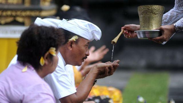 Pemuka agama Hindu memercikkan air suci saat persembahyangan bersama di Pura Luhur Candi Narmada Tanah Kilap, Denpasar, Bali, Jumat (31/01) untuk memohon agar Bali dijauhkan dari penyebaran virus Corona.