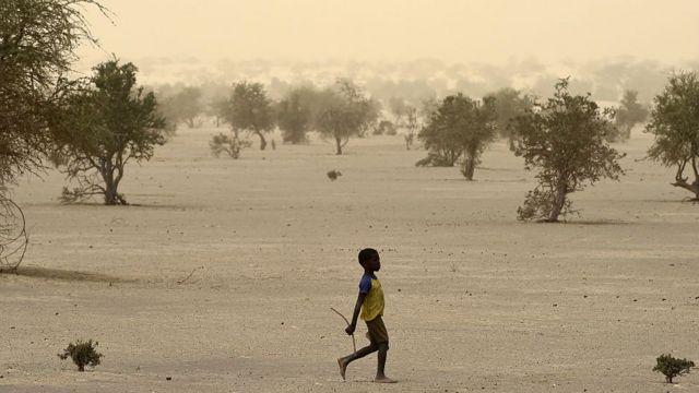 Un niño camina en una zona desértica en Mali.