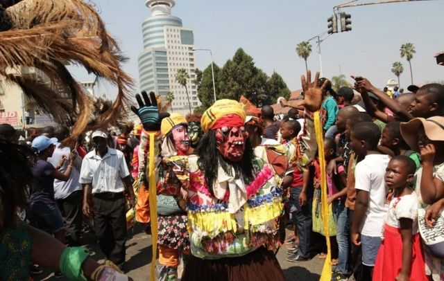 On Saturday a child looks on bemused as a Malawian traditional dancer marches during Harare international carnival...