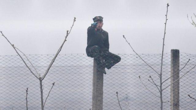 ทหารเกาหลีเหนือนั่งอยู่ที่ชายแดนระหว่างเกาหนีเหลือและจีน
