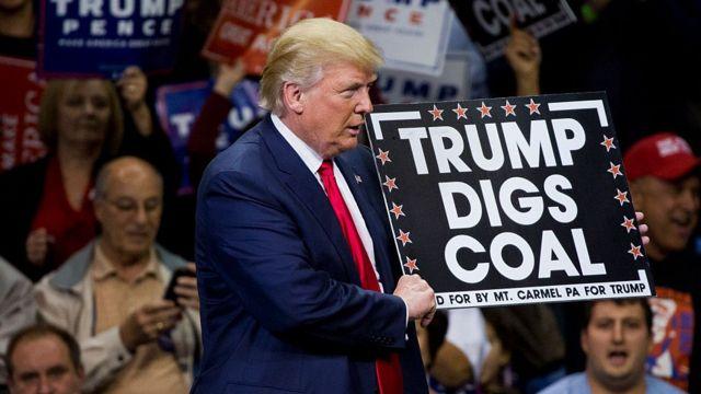 """Donald Trump sostiene un cartel que dice """"A Trump le gusta el carbón""""."""