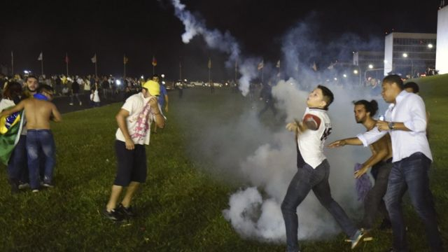 Demonstrators return tear gas to riot police during a protest against corruption in front of the Congress building in Brasilia on 16 March 2016.