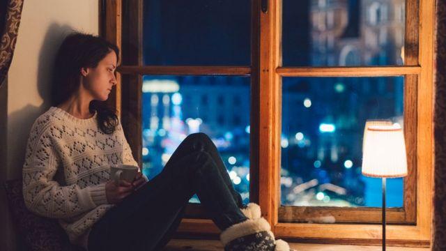 Una mujer sentada frente a su ventana