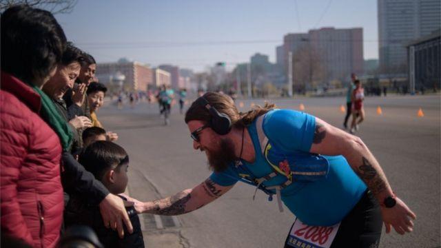 한 외국인 마라톤 참가자가 평양의 길가에서 어린이에게 말을 걸고 있다