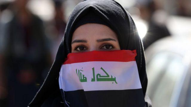 عراقية ترتدي كمامة على شكل علم الدولة