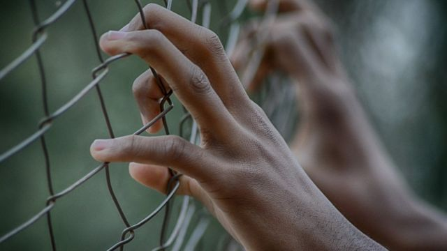 Hand dey hold prison fence