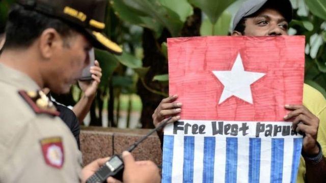 Seorang pengunjukrasa membawa simbol bendera Bintang Kejora menuntut pemisahan Papua dari Indonesia.