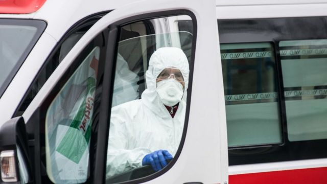 Un trabajador del hospital con equipo de protección se encuentra junto a una ambulancia en Padua, Italia