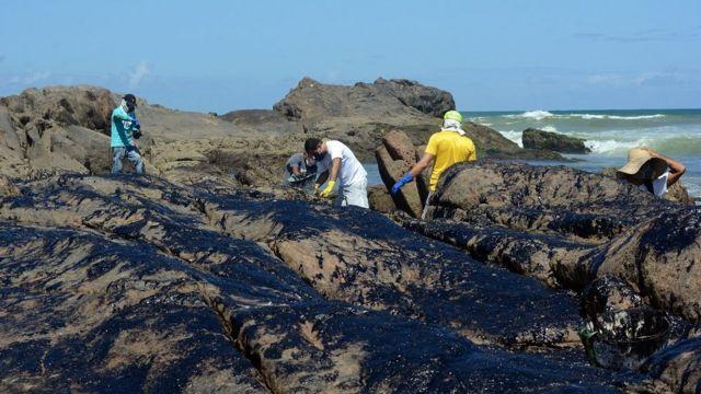 Voluntários e funcionários públicos limpam manchas de óleo em pedras