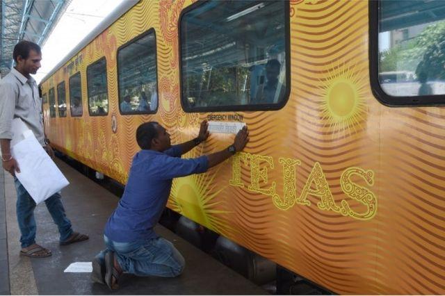 Maafisa wa treni wabandika karatasi ya ujumbe kwenye dirisha ya treni Tejas Express.