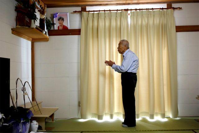 Ryuichi Nagayama prays at an altar at his home