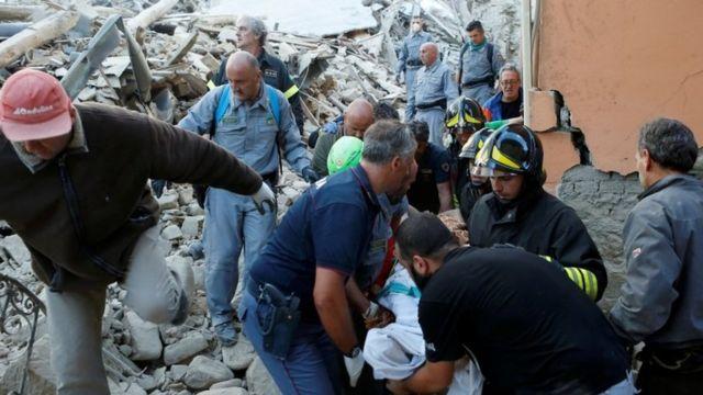 被害者を運び出す救助作業員。24日、イタリア・アマトリーチェ。