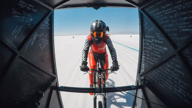 Denise Muller pedaleando en un suelo de sal, unida a un arrastrador.