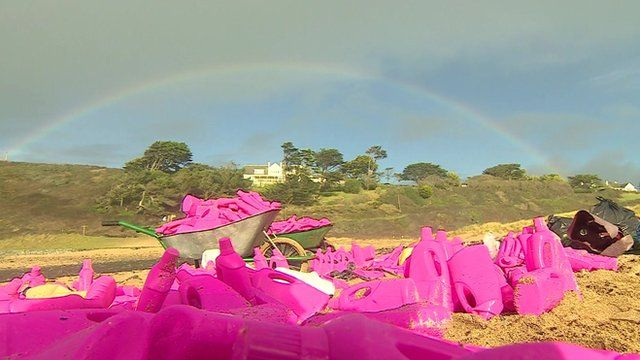 Pink bottles washed up under a rainbow, on Poldhu Cove