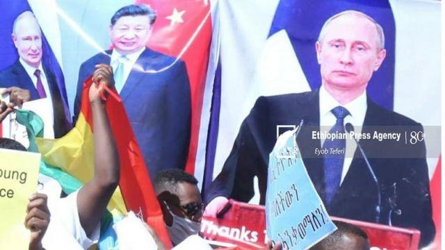 Abantu bamwe bari bitwaje ibyapa bisingiza Perezida Vladimir Putin w'Uburusiya na Xi Jinping w'Ubushinwa