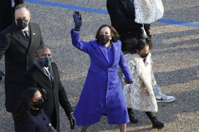 Vice President Kamala Harris waves ashe walks with Second Gentleman Doug Emhoff