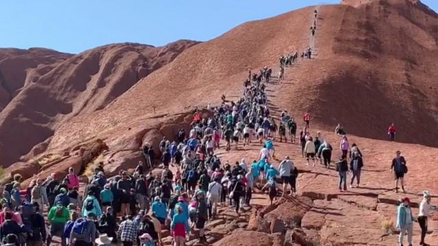 A crowd of climbers scaling Uluru on 2 October 2019