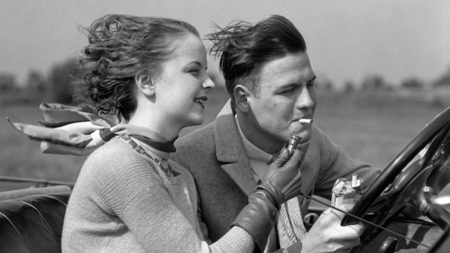 A young woman lights a cigarette for a young man driving a converible