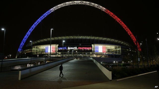 Wembley Stadium arch illuminated in the French tricolour at night