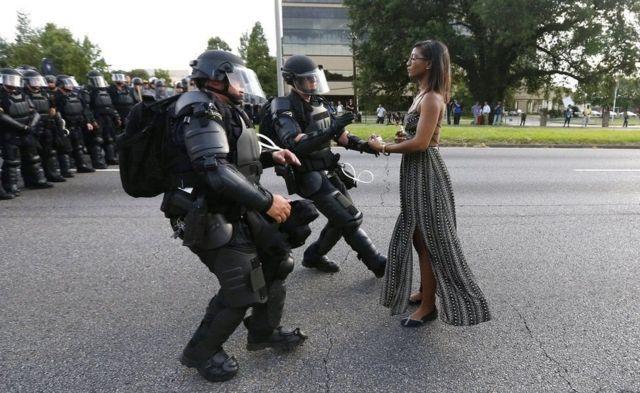 Fotógrafo de Nova Orleans registrou imagem de uma jovem negra de vestido, de pé e aparentando calma diante do que parece ser a chegada esbaforida de dois policiais armados e trajando equipamento completo de choque. A foto viralizou internacionalmente.