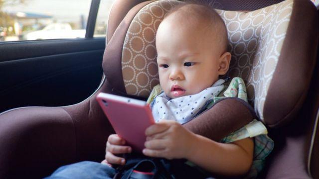 Criança pequena olha para um celular