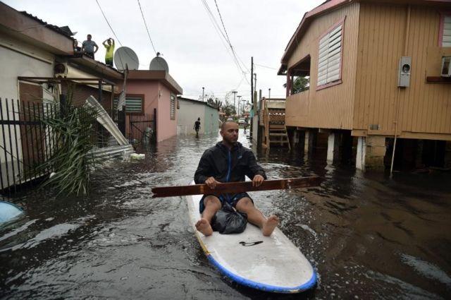 Un vecino navega por las calles inundadas con su tabla en Puerto Rico.