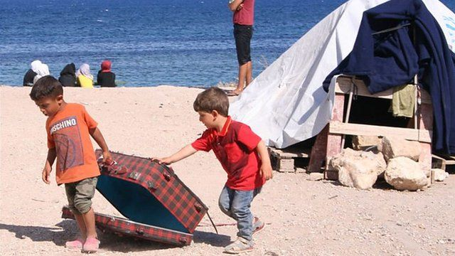 Refugee children play on the beach