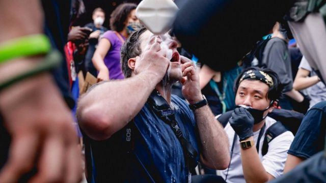 Protesters use milk to treat the sting of tear gas in New York City
