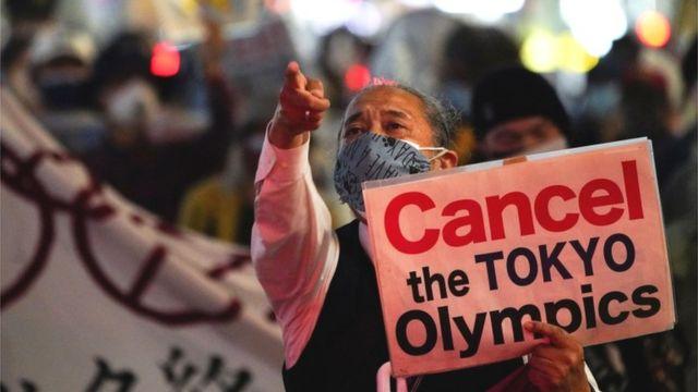 Homem segura cartaz com os dizeres 'Cancelem a Olimpíada de Tóquio'
