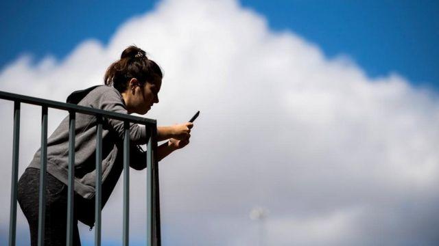 Mulher olha no celular em uma sacada