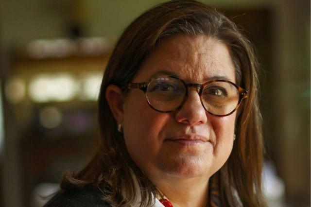 Laurie Ann Ximénez-Fyvie, uma mulher branca, de cabelos castanhos e que usa óculos marrons, olha para a câmera sorrindo