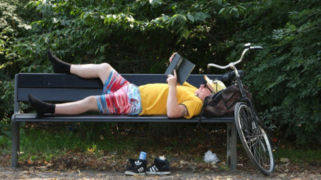 Man reading next to his bicycle on a park bench in Amsterdam.